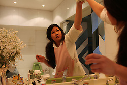 A Filipino domestic worker cleans her employers' bathroom mirror.