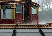 © Licensed to London News Pictures. 19/04/2012. London, UK .Rain bounces of the barge. The Royal barge Gloriana is  lowered into the River Thames today for the first time. Gloriana was designed to resemble vessels in Canaletto's famous painting of an 18th century river pageant on the Thames Gloriana will be rowed by eighteen oarsmen, including Britain's Olympian Sir Steven Redgrave. It will lead a pageant of more than 1,000 boats will sail down the Thames on June 3 to mark the 60th anniversary of Her Majesty's reign . Photo credit : Stephen Simpson/LNP