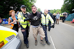 © London News Pictures. 19/08/2013. Balcombe, UK. A man being detained by police as activists clash with police outside to the Cuadrilla drilling site in Balcombe, West Sussex on a day of of civil disobedience organised by campaign group No Dash For Gas. Cuadrilla has temporarily ceased drilling at the site, which has been earmarked for fracking, under advice from the police. Photo credit: Ben Cawthra/LNP