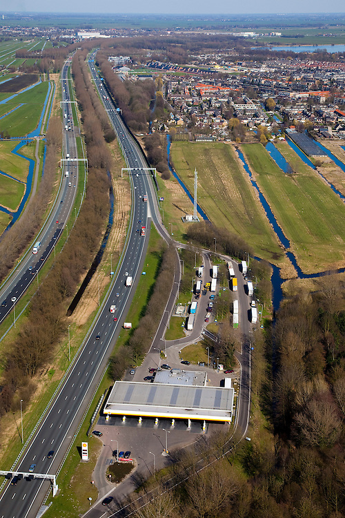 Nederland, Zuid-Holland, Reeuwijk, 20-03-2009. Verzorgingsplaats De Andel aan snelweg A12 bij Gouda, met tankstation en geparkeerde vrachtauto's. De A12 is zeer ruim opgezet en heeft aparte rijbanen. Portalen boven de weg voorzien van matrixborden en ANWB-borden sturen het verkeer. Fuel station on the motorway A12 with parked trucks. The A12 is very spacious and has separate lanes. Matrix signs and ANWB signs guide the traffic..Swart collectie, luchtfoto (toeslag); Swart Collection, aerial photo (additional fee required); .foto Siebe Swart / photo Siebe Swart