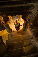 A female tourist near the base of some stairs in a Jain Temple within the Jaisalmer Fort, Jaisalmer, Rajasthan, India.