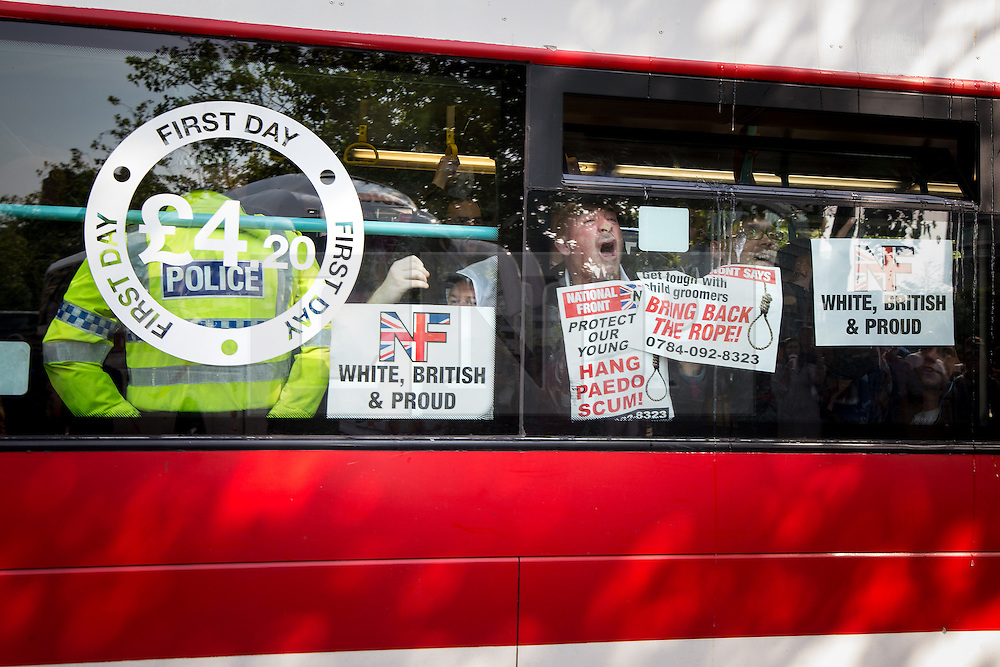 "© Licensed to London News Pictures . 22/08/2015 . Manchester , UK . Demonstrators are driven away on a coach . Far-right nationalist group , "" North West Infidels "" and Islamophobic , anti-Semitic and white supremacist supporters , hold a rally in Manchester City Centre . Photo credit : Joel Goodman/LNP"