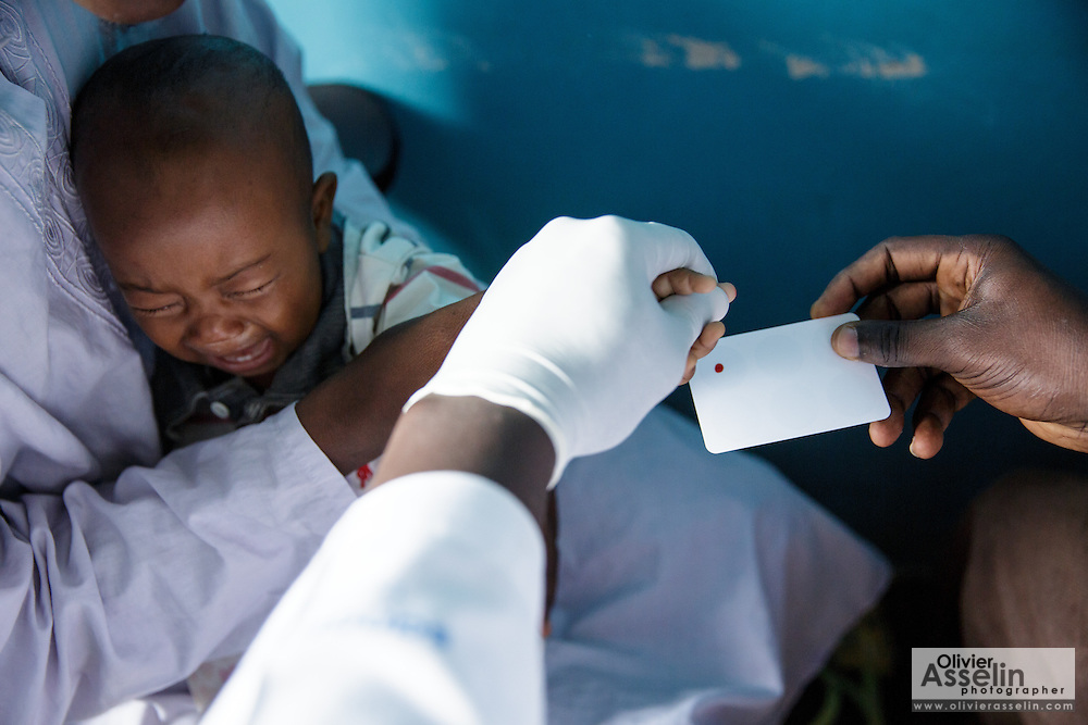 A lab technician gets a blood sample from Diallo Mamadou Kalidou, 9 months, who suffers from anemia and malaria, while he sits on his father Diallo Amadou, 25, at the Libreville health center in Man, Cote d'Ivoire on Wednesday July 24, 2013.