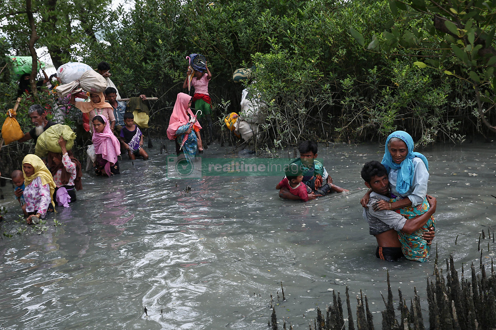 September 7, 2017 - Cox'S Bazar, Bangladesh - Rohingya people walk through water after crossing the border into Bangladesh by boat across the naf river at teknaf, Bangladesh.  September 7, 2017. Tens of thousands more people have crossed by boat and on foot into Bangladesh in the last two weeks as they flee violence in western Myanmar. (Credit Image: © Mushfiqul Alam/NurPhoto via ZUMA Press)