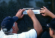 A traces a name from the Vietnam Veterans Memorial wall November 11, 1996 in Washington, DC.