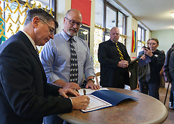 "President Thomas Krise signs a ""Partners for Veteran Supportive Campuses"" memorandum of understanding with Gary Condra, deputy director of the Washington Department of Veteran Affairs to his right on Veterans Day at PLU, Friday, Nov. 11, 2016. (Photo: John Froschauer/PLU)"
