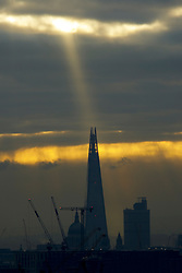 © Licensed to London News Pictures. 06/01/2017. London, UK. A shaft of sunlight is seen over the Shard from Parliament Hill during the sunrise on Hampstead Heath in north London on a cold winter morning of Friday, 6 January 2016. Photo credit: Tolga Akmen/LNP