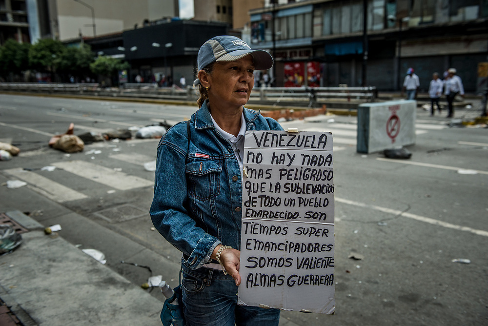 CARACAS, VENEZUELA - JULY 30, 2017:  A woman proetests infront of a street barricade built by anti-government protesters who oppose today's election for a new National Constituent Assembly. Many fear that today's election for a new National Constituent Assembly will turn Venezuela similar to Cuba. Lines to vote for the new National Constituent Assembly's candidates were significantly shorter across Caracas than those of the opposition's July 16th symbolic vote against the new assembly. Nonetheless, the government reported on state television that millions had turned out to vote. Opponents of the government criticize President Maduro for calling for this election - saying the new assembly is a power grab, and will be a puppet of the President - the only candidates on the ballot are government loyalists. Critics also fear the new assembly will turn the country into a dictatorship, re-write the constitution and wipe out the democratically elected and opposition controlled congress. There have been widespread reports of voter intimidation, and of the government threatening state workers and citizens that receive government benefits like subsidized food - who report the government telling them they are obligated to vote, and if they don't, they will lose their jobs and benefits. Thousands have taken to the streets to protest the election in the days leading up to the July 30th vote.  PHOTO: Meridith Kohut for The New York Times
