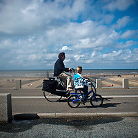vader en zoon fietsen langs de kust in Katwijk. A father and a son riding a bike along the shores of Katwijk.