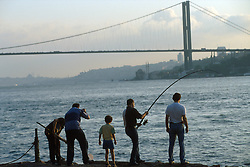 TURKEY ISTANBUL JUL02 - Turkish hobby fishermen share a moment of excitement in front of the first Bosphorus Bridge, built in 1974. It is the fourth largest bridge in the world. and connects the European and Asian parts of Istanbul and is one of the most heavily used traffic ateries in Turkey...jre/Photo by Jiri Rezac..© Jiri Rezac 2002..Contact: +44 (0) 7050 110 417.Mobile:   +44 (0) 7801 337 683.Office:    +44 (0) 20 8968 9635..Email:     jiri@jirirezac.com.Web:     www.jirirezac.com