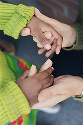 Close up of young girl holding adult's hands,