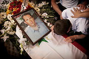 March 18 , 2012-Damascus , Syria : A young man cries on his father's coffin during a funeral for tens of victims who died due a explosion targeted Al Jamarek area in Damascus on march 17, 2012.