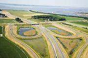 Nederland, Zeeland, Terneuzen, 04-07-2006;  het verkeersplein aan de Herbert Dowweg, ten Westen van Terneuzen, is onderdeevan de toerit tot de Westerscheldetunneen geeft aansluiting op het landelijk wegennet; het verkeersplein is een half klaverblad; de tunneis gekomen in plaats van de veerdiensten tussen Zeeuws- Vlaanderen en Zuid-Beveland; Zeeuwsch-Vlaanderen, landschapsarchitectuur, planologie, verkeer en vervoer, tol, privaat publieke samenwerking, PPS, mobiliteit, auto, infrastructuur, milieu; zie ook andere (lucht)foto's van deze lokatie, deevan de serie Panorama Nederland.luchtfoto (toeslag); aerial photo (additional fee required); .foto Siebe Swart / photo Siebe Swart