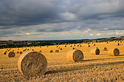 Straw bales below a stormy sky, Swinbroo, The Cotswolds, United Kingdom RESERVED USE - NOT FOR DOWNLOAD -  FOR USE CONTACT TIM GRAHAM