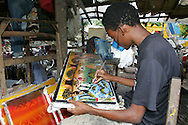A tinga-tinga painter at the Mwenge craft cooperative in Dar es Salaam, Tanzania.