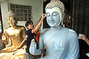 Workers painting a Buddha statue in Bangkok, Thailand.