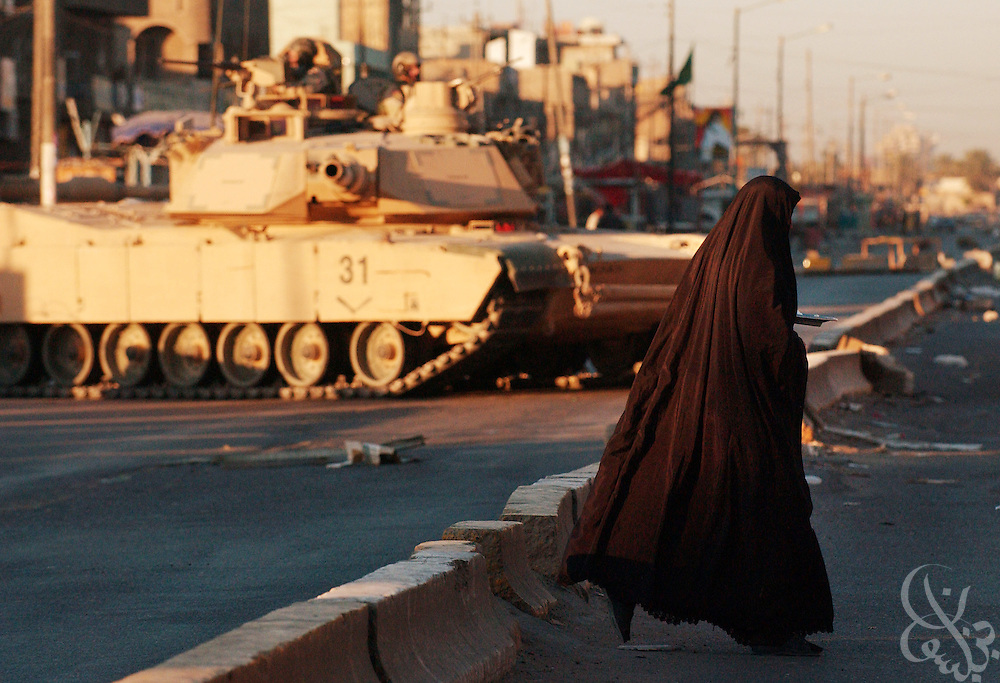 An Iraqi woman crosses a tank blocked street following April 5, 2004 clashes in the sprawling Iraqi Shia slum of Sadr City in eastern Baghdad.  Seven U.S. soldiers and more than 50 Iraqis were killed in the clashes between Coalition forces and supporters of the controversial Shia cleric Moqtada al-Sadr overnight. ..