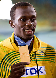 Usain Bolt of Jamaica receives the gold medal during the medal ceremony for the men's 200 Metres Final during day seven of the 12th IAAF World Athletics Championships at the Olympic Stadium on August 21, 2009 in Berlin, Germany. (Photo by Vid Ponikvar / Sportida)
