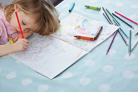 Girl (3-4) resting head on arm colouring in book elevated view