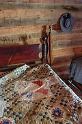 A dulcimer and felt hat hang by a quilted bed in a cabin interior at Humpback Rocks Mountain Farm, a restored 1890s farmstead open to the public at Milepost 5.8 on the Blue Ridge Parkway, in Virginia, in the Blue Ridge Mountains (a subset of the Appalachian Mountains), USA. In summer, costumed interpreters demonstrate 1890s southern Appalachian mountain life. European settlers of the Appalachian Mountains forged a living from abundant native materials: hickory, chestnut, and oak trees provided nuts for food, logs for building, and tannin for curing hides; and the rocks were used as foundations, chimneys and stone fences. This farm was originally a Land Grant tract dispensed by the Commonwealth of Virginia to induce pioneers to settle; and later it became known as the William J. Carter Farm. The scenic 469-mile Blue Ridge Parkway was built 1935-1987 to aesthetically connect Shenandoah National Park (in Virginia) with Great Smoky Mountains National Park in North Carolina, following crestlines and the Appalachian Trail.