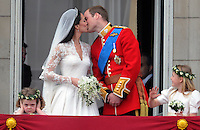 Prince William, Duke of Cambridge and Catherine, Duchess of Cambridge kiss as bridesmaid Grace van Cutsem covers her ears against the noise and bridesmaid Margarita Armstrong--Jones looks delighted  on the balcony at Buckingham Palace in London, England following their wedding at Westminster Abbey on April 29, 2011