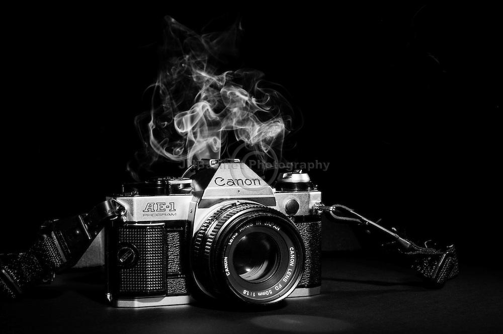 Smoke billows upward from behind an old Canon SLR