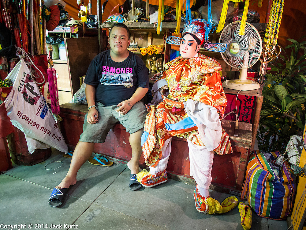 "26 NOVEMBER 2014 - BANGKOK, THAILAND:  Performers wait for the Chinese opera to start at the Chow Su Kong Shrine in the Talat Noi neighborhood of Bangkok. Chinese opera was once very popular in Thailand, where it is called ""Ngiew."" It is usually performed in the Teochew language. Millions of Chinese emigrated to Thailand (then Siam) in the 18th and 19th centuries and brought their culture with them. Recently the popularity of ngiew has faded as people turn to performances of opera on DVD or movies. There are about 30 Chinese opera troupes left in Bangkok and its environs. They are especially busy during Chinese New Year and Chinese holidays when they travel from Chinese temple to Chinese temple performing on stages they put up in streets near the temple, sometimes sleeping on hammocks they sling under their stage.     PHOTO BY JACK KURTZ"