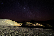Under a moonless night sky in Death Valley California, headlights from a passing car light the barren landscape at Zambriske Point making it seem as though one is standing on another planet looking out into the universe.  The upper left star cluster is the Pleiades (also known as the Seven Sisters or Messier object 45) which is a 100 million year old formation approximately 130 parsecs (424 light-years) from earth.<br /> <br /> Zabriskie Point is part of the Amargosa Range located on the eastern side of Death Valley.  The area is noted for its erosional landscape, composed of sediments from Furnace Creek Lake, which dried up 5 million years ago&mdash;long before Death Valley came into existence.  This ancient lake began forming approximately nine million years ago. During the several million years of the lake's existence, sediments composed of saline muds, mountain gravels, and ashfalls from the then-active Black Mountain volcanic field collected at the bottom of the lake.<br /> <br /> Camels, mastodons, horses, carnivores, and birds left tracks in the lakeshore muds, along with fossilized grass and reeds. Borates were concentrated in the lakebeds from hot spring waters and decomposition of rhyolite in the nearby volcanic fields. Indeed, the location is named after Christian Brevoort Zabriskie, vice-president and general manager of the Pacific Coast Borax Company in the early 20th century. The company's twenty-mule teams were used to transport borax from its mining operations in Death Valley.