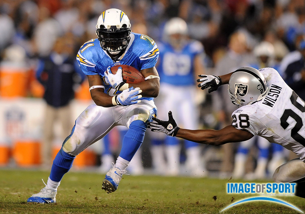 Dec 4, 2008; San Diego, CA, USA; San Diego Chargers running back LaDainian Tomlinson (21), left, tries to elude Oakland Raiders safety Gibril Wilson (28) in the second half at Qualcomm Stadium. The Chargers defeated the Raiders 34-7.