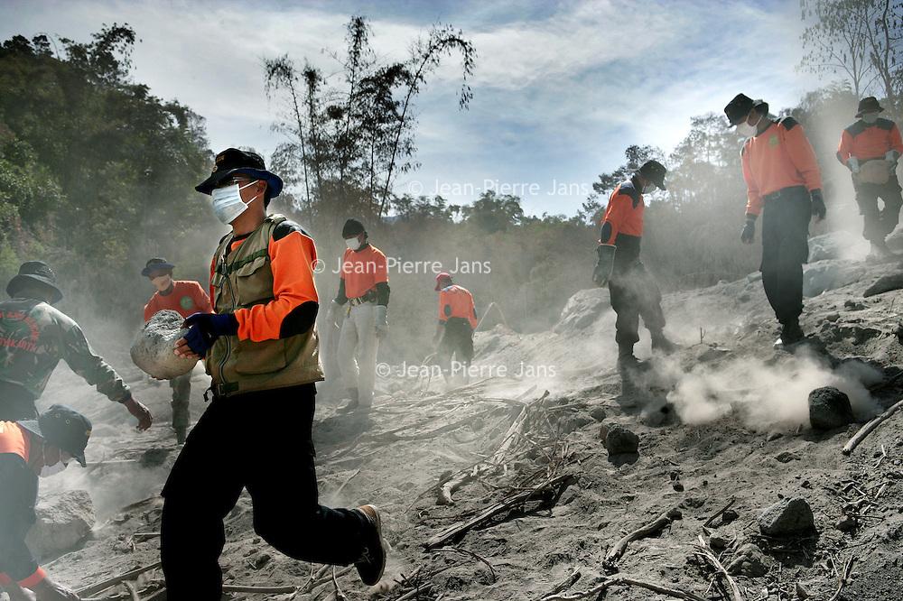 Indonesie.Jogjakarta.Juni 2006.<br /> Hulpverleners en locale mensen uit het natuurrampgebied rond Jogjakarta helpen mee de weg vrij te maken van lagen vulkaanas als gevolg van de recente vulkaanuitbarsting van de vulkaan de Merwati.<br /> Foto:Jean-Pierre Jans/de Volkskrant