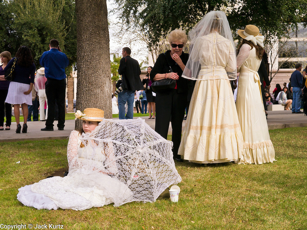 14 FEBRUARY 2012 - PHOENIX, AZ:  MCKENNA COOK, 17, sits on the lawn in front of the Arizona Supreme Court while she waits for her mother's wedding to start. Ninetysix couples got married in a mass ceremony on the steps of the Arizona Supreme Court to mark the Valentine's Day holiday. The wedding was also an occasion to mark Arizona's centennial of statehood.     PHOTO BY JACK KURTZ