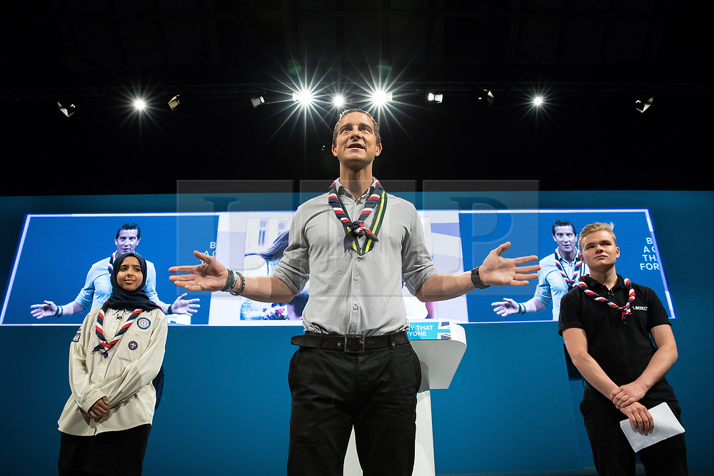 © Licensed to London News Pictures . 03/10/2017 . Manchester , UK . FERDOUS AL-AUDHALI (22 from Solihull) , Chief Scout BEAR GRYLLS and JACK WHITE (20 from South Shields) on stage ahead of the Home Secretary , during day three of the Conservative Party Conference at the Manchester Central Convention Centre . Photo credit : Joel Goodman/LNP