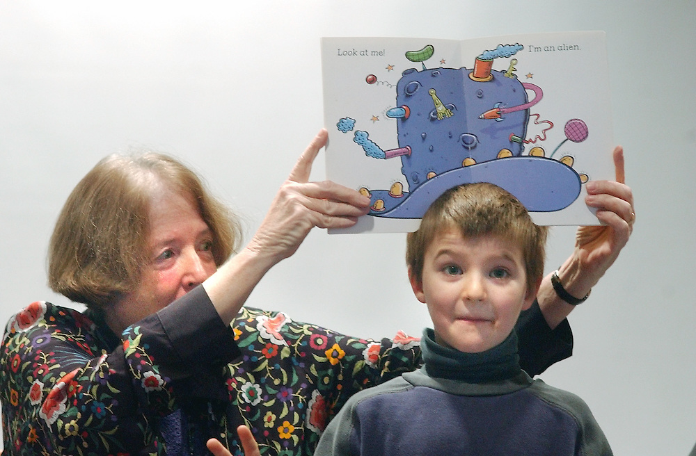 Rockport: Wendy Pierson puts a book of hats on the head of Michael Sullivan, 7, of Rockport during Story Time at Rockport Public Library Wednesday.  (Photo by Mike Dean/Gloucester Daily Times). Wednesday, January 15, 2003 (NOTE: THIS IS A DIGITAL CAMERA IMAGE)..**************************************.Filter: Min (QMPro: Red Radius:0/Blue Radius:6/Desp.).USM: Normal (Amt:200/Radius:0.3/Thresh:2).File Size: 7.51MB.Original file name: DSC_0599.JPG