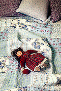 an old doll on a vintage bed