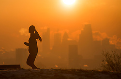 © Licensed to London News Pictures. 12/12/2017. London, UK. A jogger at sun rise on Hampstead Heath in north London as the sun rises over the city of London on a freezing morning. Temperatures across the the UK dipped overnight with some regions expected to drop to -13C (9F). Photo credit: Ben Cawthra/LNP