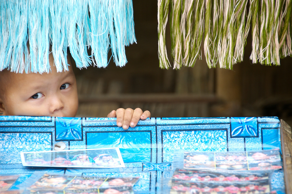 Young karen hill tribe child peaking from behind his mothers stall.