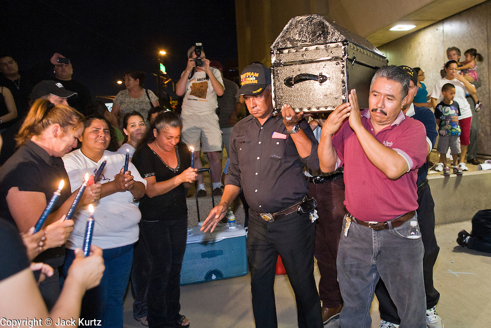 11 OCTOBER 2010 - PHOENIX, AZ: Protesters hold a mock funeral for Daniel Rodriguez during a vigil for the man, who was shot by Phoenix police. About 300 people gathered at the Phoenix Police Department headquarters building Monday night to protest the shooting of Daniel Rodriguez and his dog. The officers responded to a 911 call made by Rodriguez' mother. A scuffle ensued when they arrived and Phoenix police officer Richard Chrisman shot Rodriguez, who was unarmed, and his dog. Chrisman then allegedly filed a false report about the event. He has been arrested on felony assault charges. The event has angered some in the Latino community and they have held a series of protests at the police headquarters. They want Chrisman charged with murder.  PHOTO BY JACK KURTZ