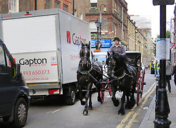 © Licensed to London News Pictures. 12/09/2017. London, UK. A horse and carriage move past modern day traffic a new television series 'Vanity Fair' is filmed in Sptalfields in London. The mini series is being made for ITV and Amazon Prime and stars Tom Bateman and Michael Palin. Photo credit: Graham Long/LNP