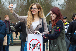 "Nationalist group Pro Great Britain hold a 'freedom of speech' protest at Hyde Park Corner with a small number of anti-fascists counter protesting. The demonstration comes after two speakers Austrian Martin Sellner and American Brittany Pettibone from Generation Identity, ""a Europe-wide patriotic youth movement that promotes the values of homeland, freedom and tradition through peaceful activism, political education, and community & cultural activities"" were refused entry to the UK by border officials. PICTURED: A woman films herself and a friend as they await the beginning of the rally. London, March 11 2018."