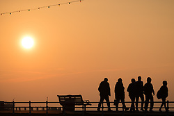 © Licensed to London News Pictures. 23/10/2016. Southsea, UK.  People walking along Southsea promenade. A fine start to the day at sunrise in Southsea this morning, where the Great South Run 2016 event is being held today.  Photo credit: Rob Arnold/LNP