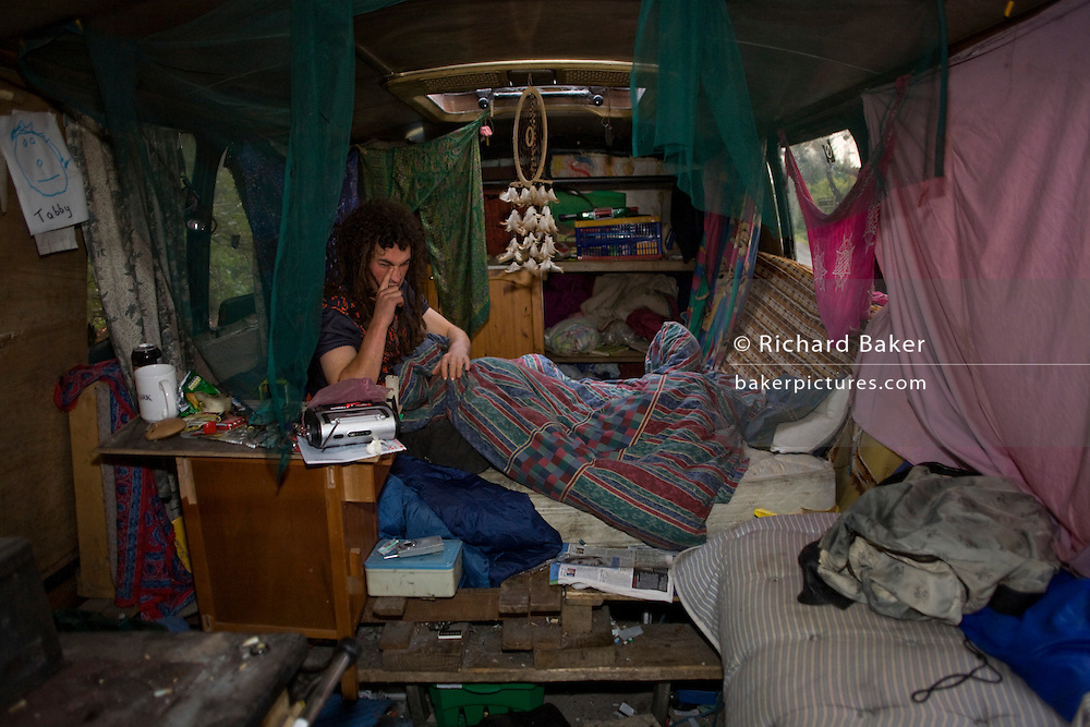 Activist 'Hoosie' aka Robert House, wakes up early on a Sunday morning in his bus-turned-home at the Faslane Peace Camp.