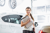 Portrait of confident female mechanic with clipboard in car workshop