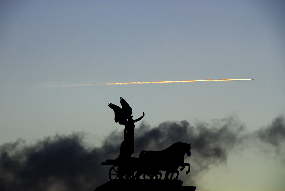 An aircraft cuts a fiery cloud of smoke through the sky at sunset with a winged statue in a chariot pulled by horses points in the forground