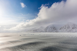 In a fjord in Svalbard, Anon encountered conditions he'd never seen before: waves newly-forming slush ice.  Beyond the solid waves was a field of pancake ice, and further in the distance, a clearing storm.  Using an ultra-wide angle lens, he composed a shot to capture Svalbard's ever-changing landscape.