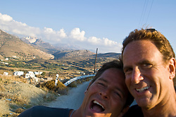 Two men posing for a photograph with the backdrop of Naxos, Greece behind them