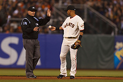 August 9, 2011; San Francisco, CA, USA;  San Francisco Giants shortstop Orlando Cabrera (right) hands the ball to MLB umpire Ed Hickox (left) during the fifth inning against the Pittsburgh Pirates at AT&T Park. San Francisco defeated PIttsburgh 6-0.