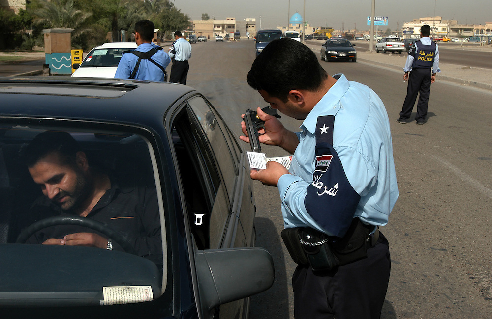 An Iraqi Policeman checks the permit of a man carring a fire arm in his car at a check point in the al-Bahya area of Baghdad..Baghdad, Iraq. 28/04/2004.Photo © J.B. Russell