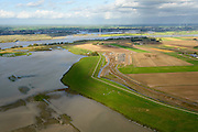 Nederland, Noord-Brabant, Werkendam, 23-10-2013; Ruimte voor de Rivier project Ontpoldering Noordwaard, rivier de Nieuwe Merwede aan de horizon. Het deel links is reeds ontpolderd, rechts het gedeelte in ontwikkeling waar boerderijen en particuliere huizen op nieuw opgeworpen terpen gebouwd worden.<br /> Voor dit project worden delen van de polder ontpolderd en de dijken worden verlegd en/of verlaagd waardoor bij hoogwater het rivierwater ook door de polder sneller weg kan stromen richting zee. Gevolg van de ingrepen is ook dat de waterstand verder stroomopwaarts zal dalen. Boven in beeld het deel van de polder wat al ontpolderd is. Kunstwerk  De Wassende Maan van kunstenaar Paul de Kort linksboven.<br /> As part of the program Ruimte voor de rivier (Room for the River)  this polder Noordwaard ihas been partly depoldered, but a freshwater tidal reserve. Landart Growing Moon by artist Paul de Kort top left.<br /> luchtfoto (toeslag op standard tarieven);<br /> aerial photo (additional fee required);<br /> copyright foto/photo Siebe Swart