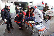An elderly woman is carried away from a Japan Self Defence Force ambulance at the Red Cross hospital in Ishinomaki, Miyagi Prefecture on 13 March, 2011. Hundreds of people have been evacuated from their homes after a magnitude 9 quake hit northeast Japan on March 11. Photographer: Robert Gilhooly