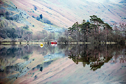 © Licensed to London News Pictures. 14/04/2016. Ullswater UK. A red boat & tree's reflect in the calm water of Ullswater lake in Cumbria this morning. Weather forecasters predict scattered showers in the south & drier in the north.  Photo credit: Andrew McCaren/LNP